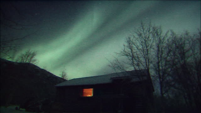 southern lights seen above silhouetted cabin and trees, antarctic - aurora australis stock videos & royalty-free footage