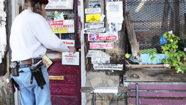 stockvideo's en b-roll-footage met southern man with firearms enters a doorway covered in propaganda posters - kleverig