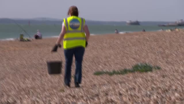 southsea beach cleanup gvs; england: portsmouth: southsea: gvs jane and mae picking up litter on beach / gv chocolate wrapper / gvs jane and mae... - rubbish stock videos & royalty-free footage