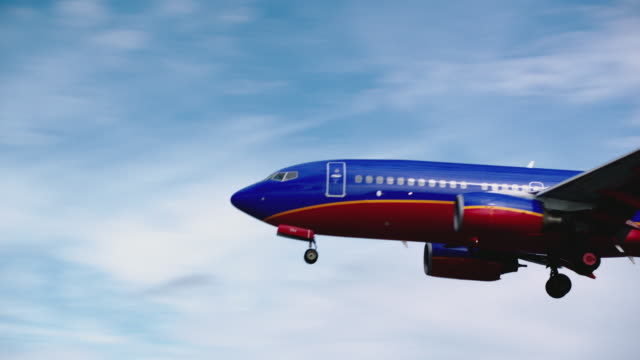 Southwest Airlines jet enters frame close-up on approach, then touches down for landing at SFO