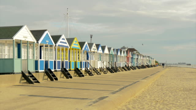southwold,row of beach huts,early morning,man walking in background,ws, - promenade stock videos & royalty-free footage
