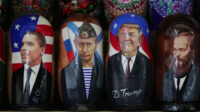 Souvenir matryoshka dolls depicting Vladimir Putin Russia's president and Donald Trump US president sit on display at a tourist stall in the city...