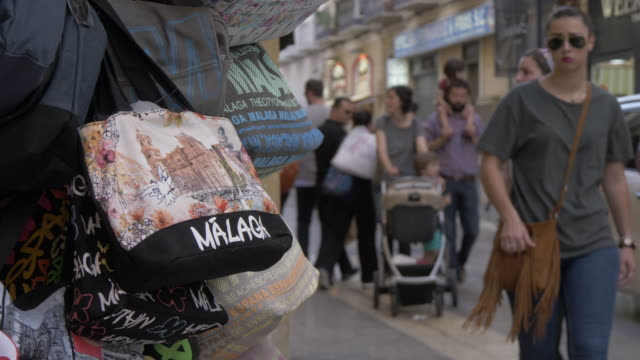souvenir shopping bags and busy street, malaga, andalucia, spain, europe - souvenir stock videos and b-roll footage