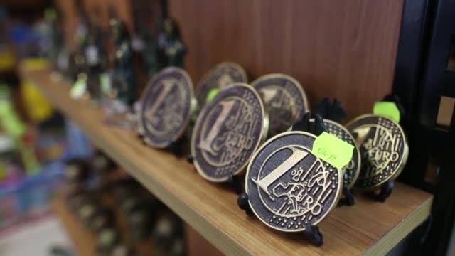 Souvenir store assistant spins clothes rack with 'I Love Cyprus' tshirts Plastic 1 euro coins sit on shelf inside souvenir shop Cyprus mementos sit...