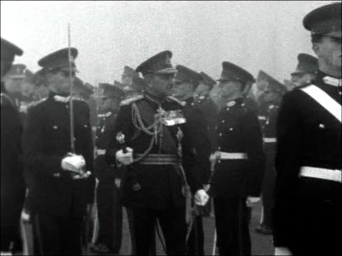 sovereign's parade at sandhurst 1956; england: surrey: sandhurst military academy: ext / foggy field marshal sir gerald templer arrives at parade and... - 光栄点の映像素材/bロール