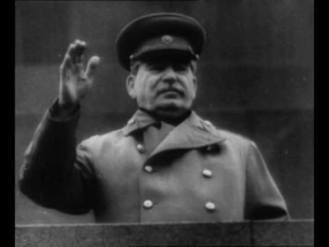 soviet leader joseph stalin smiles soviet politician mikhail kalinin sits behind him / military parade in red square / stalin waves stiffly from... - ex unione sovietica video stock e b–roll