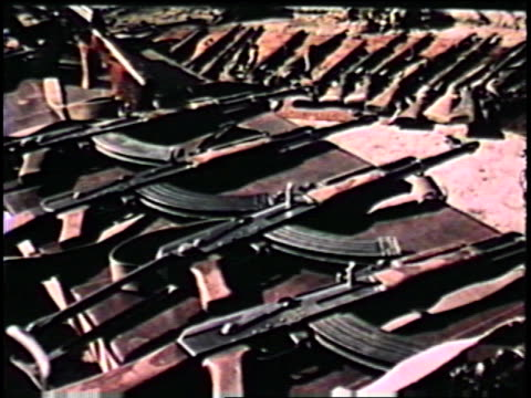 stockvideo's en b-roll-footage met soviet made armaments on display at camp ak47 rifles rocket launchers machine guns banner of the april revolution on january 01 1980 in afghanistan - raket wapen