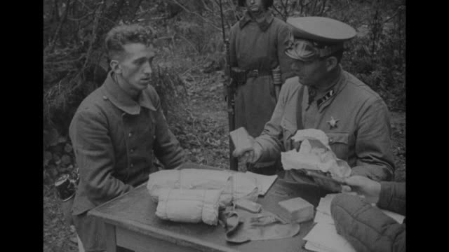 soviet officer sitting at table outdoors talking to german prisoner sitting at table next to him bundles lying on table officer picks up bundle and... - guarding stock videos & royalty-free footage