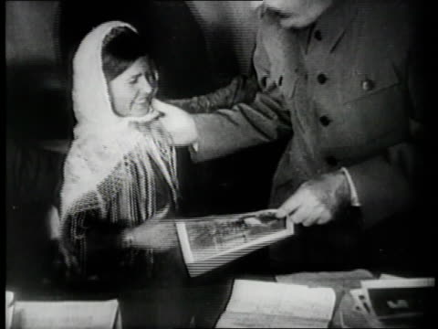 soviet peasant women smile and clap while dictator joseph stalin hands one of them a signed photograph. - dictator stock videos & royalty-free footage