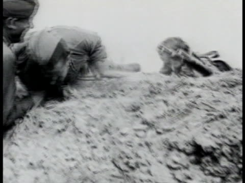 stockvideo's en b-roll-footage met soviet russian nurse helping wounded soldier into trench pulling rifle over tank driving on road graphic soldier lying on side of road smoke dust... - 1942