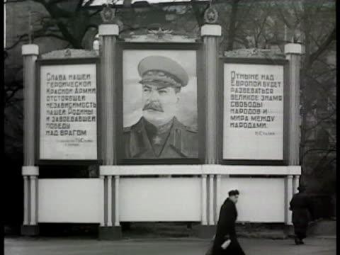 soviet russian soldiers walking in column on sidewalk. drawing of stalin on billboard w/ writting both sides of sign. russian & american officers... - 1948年点の映像素材/bロール