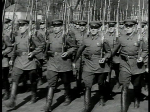 Soviet soldiers in gear w/ rifles marching in formation