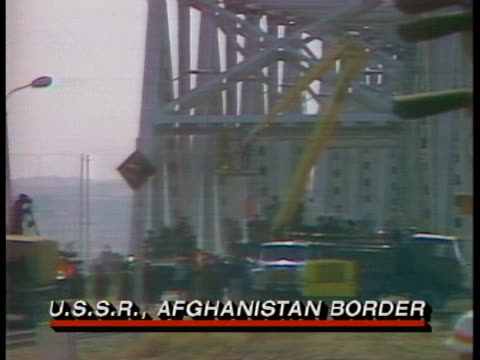 soviet tanks move along the bridge at the u.s.s.r. afghanistan border as soviet soldiers leave afghanistan . - russia stock videos & royalty-free footage