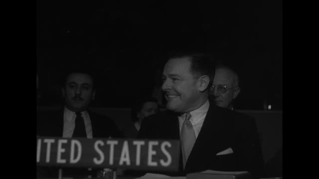 Soviet United Nations Representative Andrei Vishinsky sits in Soviet United Nations chair and listens through earphones / long shot of UN members at...