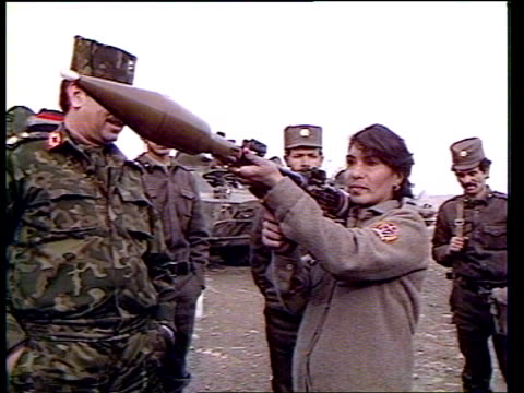 vidéos et rushes de soviet withdrawal; afghanistan: kabul : ext afghan girl in camouflage gear fires soviet assault rifle into air sof zoom in as jeep and photographers... - kaboul