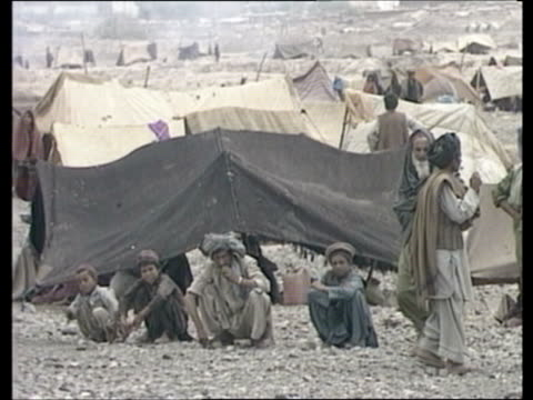 soviet withdrawal / humanitarian aid efforts 1551988 refugee camp ext afghan refugee camp as tents scattered about afghanis squatting by tent as... - refugee camp stock videos & royalty-free footage