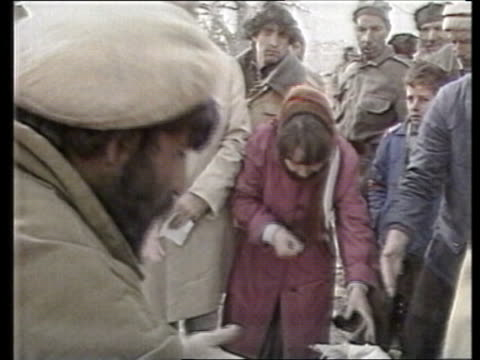soviet withdrawal / humanitarian aid efforts; tx 25.1.1989 afghanistan: kabul: ext kabul citizens arguing r-l people arguing & jostling over food... - kabul stock videos & royalty-free footage