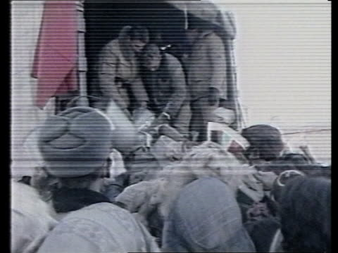 soviet withdrawal / humanitarian aid efforts tx soviet soldiers handing out flour to crowd in bv from back of truck zoom in clamouring crowd waving... - afghanistan stock videos & royalty-free footage