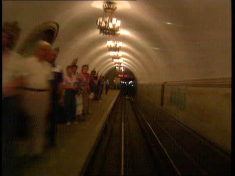 Moscow Metro GV Wide walkway with columns amp chandeliers MS Passengers along to amp fro BV Woman along away PULL OUT MS Train pulling into platform...