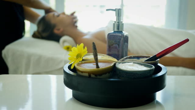Spa and massage elements, aroma salt, herbal oil, Young woman relaxing in background, Spa treatment and aromatherapy concept, Selective focus