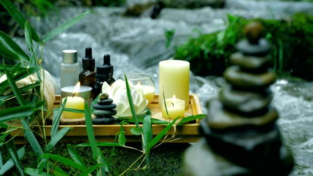 vídeos de stock, filmes e b-roll de conceito de spa com pedra zen no fluxo - folha de bambu