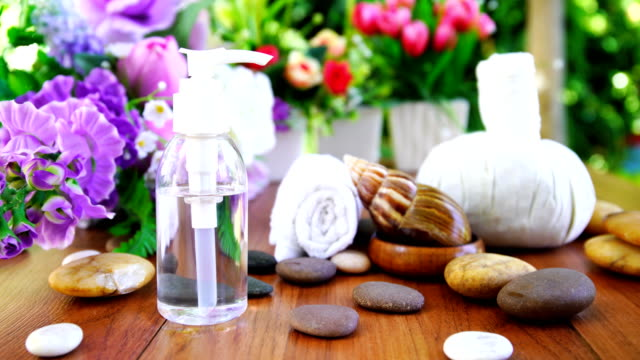 spa concept,snail and bottle collagen or serum oil, thai spa massage setting with bottle with essential oil and thai herbal compress balls - mollusk stock videos & royalty-free footage