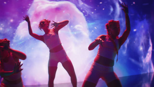 space dance. synchronized dancers performing on projection background. screening with universes and nebulas - modern dancing stock videos & royalty-free footage
