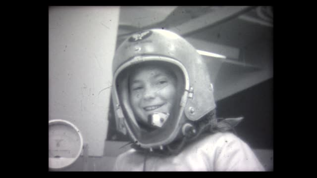 1965 space lecture with young boy astronaut climbing into space capsule - 宇宙服点の映像素材/bロール