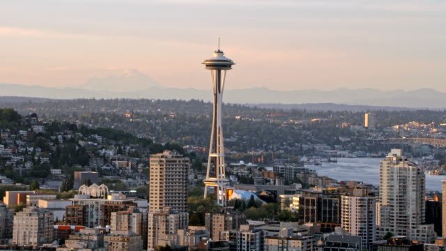 aerial space needle rising above the skyscrapers in seattle - seattle stock-videos und b-roll-filmmaterial