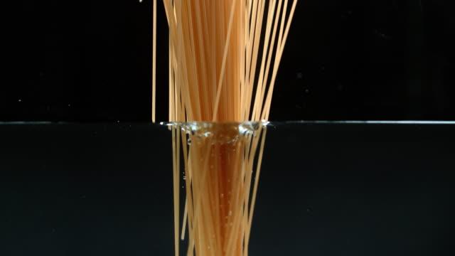 spaghetti falling down in water - super slow motion - crudo video stock e b–roll