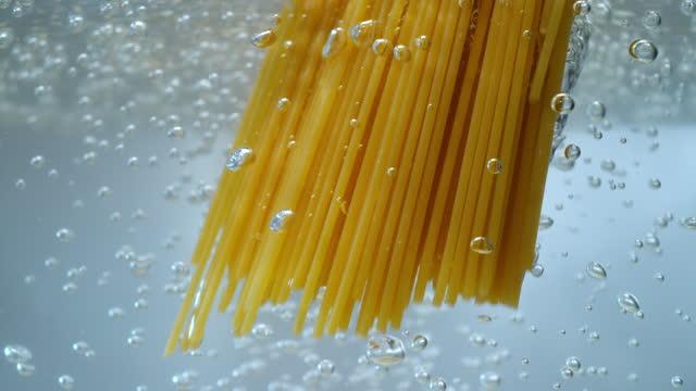 slo mo ld spaghetti falling into boiling water - spaghetti stock videos & royalty-free footage