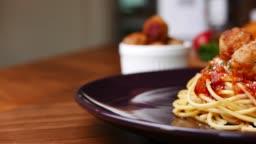 Spaghetti  Meatballs set on dinner table.