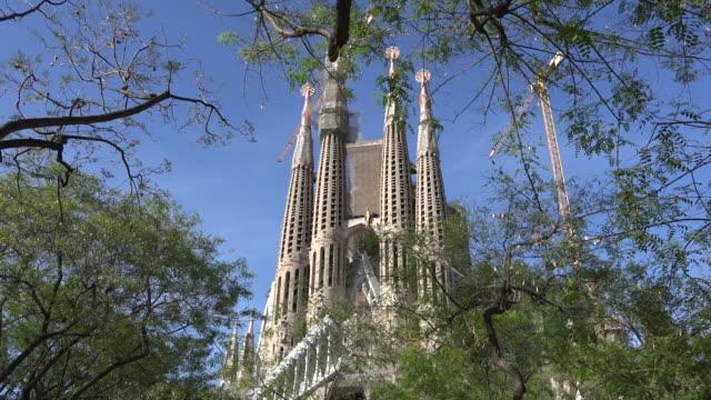 spain barcelona sagrada familia beyond trees in park - tornspira bildbanksvideor och videomaterial från bakom kulisserna