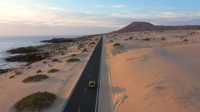 spain, canary islands, fuerteventura, aerial view of road crossing corralejo dunes natural park - nationalpark stock-videos und b-roll-filmmaterial