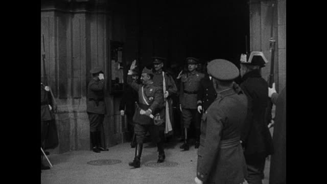 vídeos y material grabado en eventos de stock de spain dictator francisco 'el caudillo' franco in generals uniform exiting building w/ aides & officials waving to crowd guards. vs spanish... - fascismo