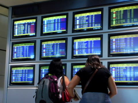 ms, spain, madrid, two women looking at airport departure board, rear view - flugpassagier stock-videos und b-roll-filmmaterial