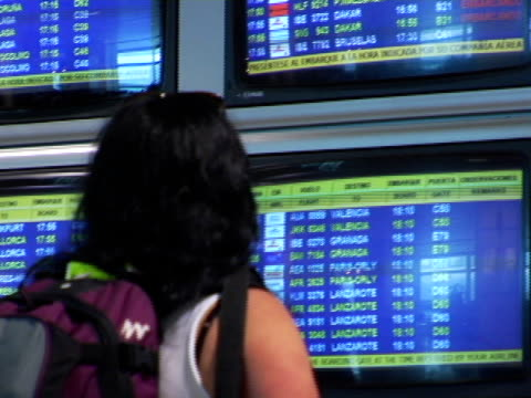 cu, spain, madrid, woman looking at airport departure board, rear view - flugpassagier stock-videos und b-roll-filmmaterial