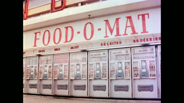 span of a huge automatic dispensing machine with numerous coin slots and sections with the name 'food o mat' across the top / cu of hand putting... - anno 1958 video stock e b–roll