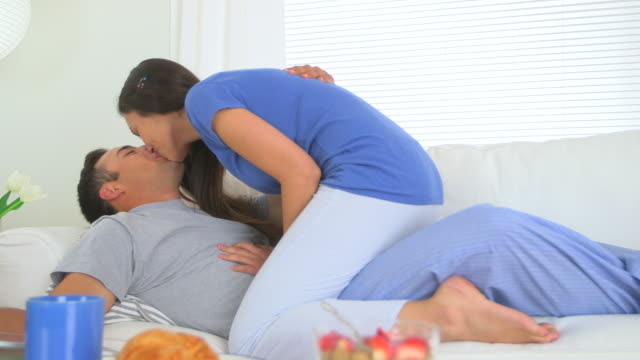 spanish couple kissing on couch - braunes haar stock-videos und b-roll-filmmaterial