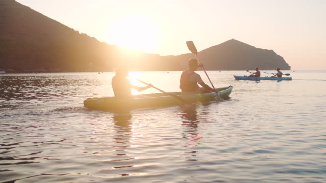 vídeos de stock e filmes b-roll de spanish couples paddling kayaks in mediterranean at dawn - kayaking