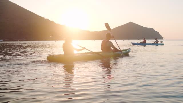 vídeos y material grabado en eventos de stock de parejas españolas remando kayaks en el mediterráneo al amanecer - remar con pala