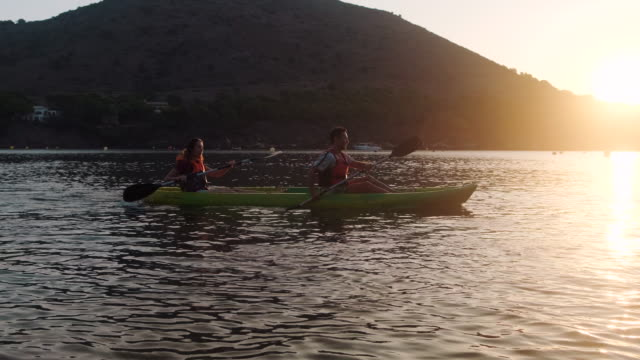 coppie spagnole pagaiare kayak nel mediterraneo all'alba - remo video stock e b–roll