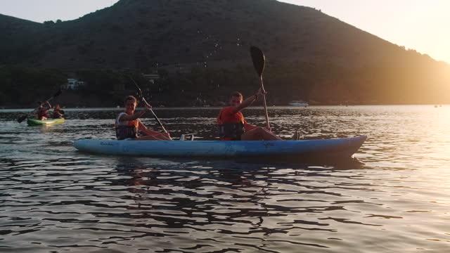 spanish couples paddling kayaks in mediterranean at dawn - kayak stock videos & royalty-free footage