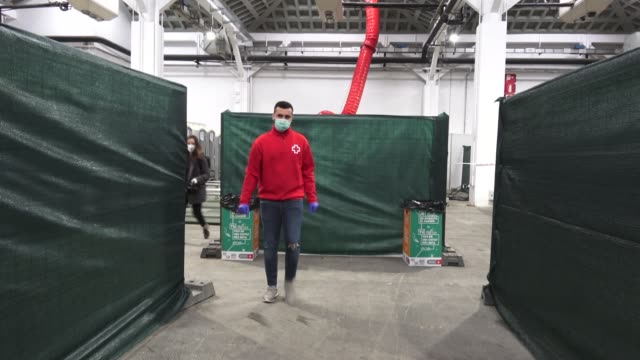 spanish cruz roja 'red cross'member is seen at the pavilion at fira de barcelona as final preparations are made before accommodating homeless people... - 赤十字社点の映像素材/bロール