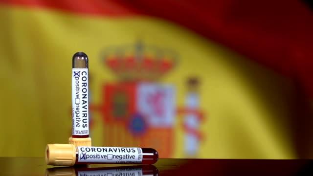 vidéos et rushes de drapeau espagnol flapping derrière les tubes d'essai de sang - espagne