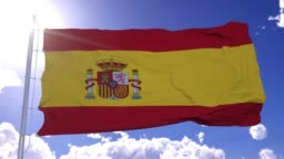 Spanish flag fluttering in the wind. National flag against a blue sky