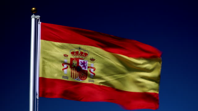 4k: spanish flag on flagpole in front of blue sky outdoors (spain) - spanish flag stock videos and b-roll footage