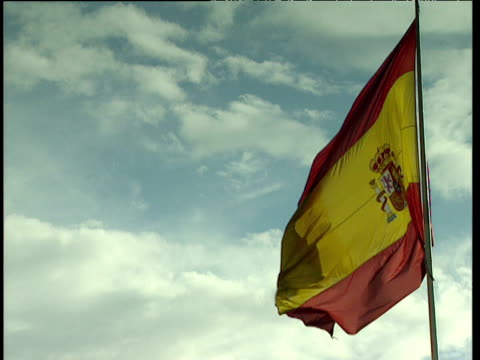 Spanish flag with crest flying in the wind against a blue and white sky