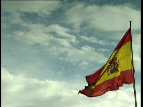 spanish flag with crest flying in the wind against a blue and white sky - スペイン国旗点の映像素材/bロール