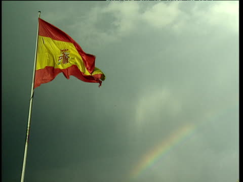 Spanish flag with crest flying in the wind against a stormy sky and rainbow.
